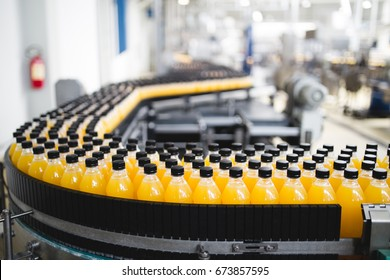 Industrial factory indoors and machinery. Robotic factory line for processing and bottling of soda and orange juice bottles. Selective focus. Short depth of field.