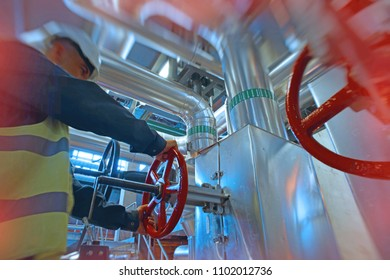 industrial factory worker turning red wheel of valve