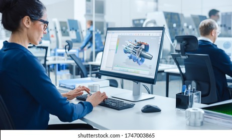 Industrial female Engineer Working on a Personal Computer, Screen Shows CAD Software with 3D Prototype of Engine. Busy Factory with Professional Workers High-Tech Machinery