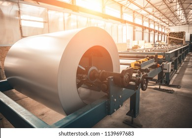 Industrial galvanized steel roll coil for metal sheet forming machine in metalwork factory workshop, sunlight toned