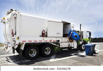 Industrial garbage truck with hydraulic lift arm under blue sky. Rear and side view. Nobody.