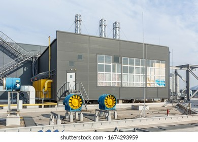 industrial gas boiler on the roof of the building, with metal chimneys against the sky.