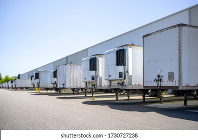 Industrial grade refrigerator and dry van semi trailers with reefer units on the front wall and without it standing at warehouse dock gates loading commercial cargo for next freight delivery