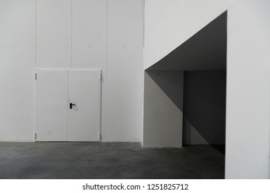 Industrial hall composition with a white door and a concrete frame seen in perspective and grey cement flooring.