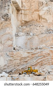 Industrial heavy machinery bulldozer at work inside Carrara marble mountain with marble rubble