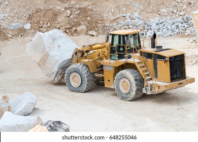 Industrial heavy machinery forklift transporting big marble block inside Carrara marble quarry in Italy