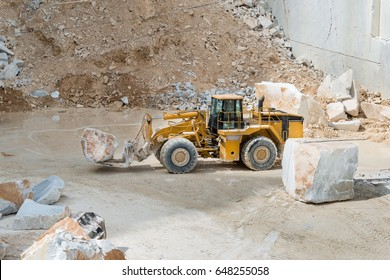 Industrial heavy machinery forklift transporting a marble block inside Carrara marble quarry in Italy