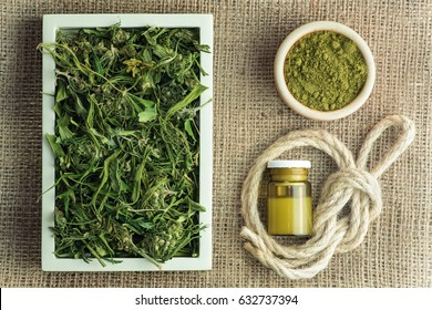 Industrial hemp plant products: tea, oil, rope and protein powder on 100% hemp fabric