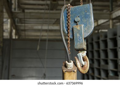 Industrial hook hanging on chain from ceiling