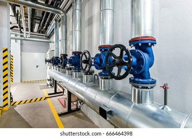 Industrial hot water valves painted blue and pipes mounted in central heating unit for factory