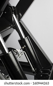 Industrial hydraulic cylinders on black machinery.