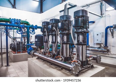 Industrial interior of water pump, valves, pressure gauges, motors inside engine room. Valve and pumps in an industrial room. Urban modern powerful pipelines and pumps, automatic control systems