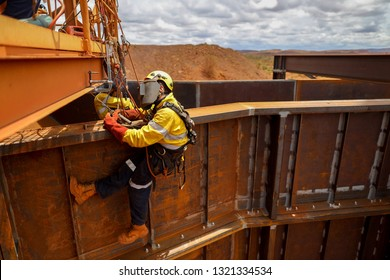 Industrial isolated rope access welder maintenance abseiler wearing fall safety body harness helmet protective equipment abseiling welding repairing structure beam construction mine site, Perth