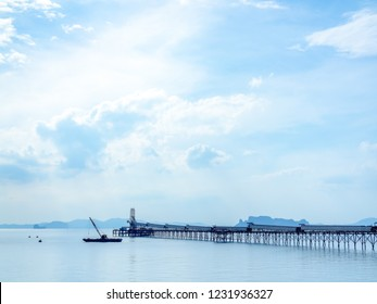 Industrial jetty for loading facility and offshore supply vessel in the sea on blue sky background with copy space.