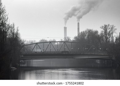Industrial landscape with bridge over Mur river and thermal power plant in the background, in Graz, Styria region, Austria, in foggy winter morning.