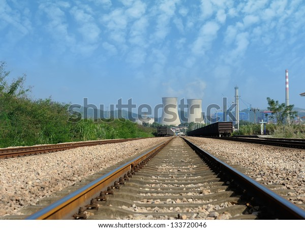 Industrial landscape with chimneys and train.,
