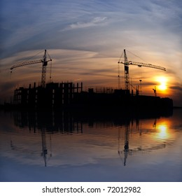 Industrial landscape. Construction cranes and concrete structure at sunset with reflection in water