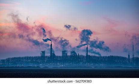 Industrial landscape at dusk with chimney's, smoke, trees and pink sky