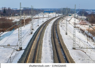 Industrial landscape - electrified railway line in the snow with lots of pillars and wires turns to the right to the railway bridge
