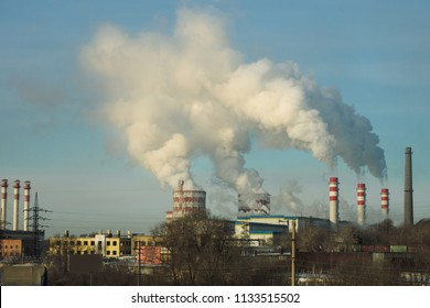 Industrial landscape with metallurgical plant, fuming pipes and white smoke. Metallurgical works with smoke. Industrial architecture.