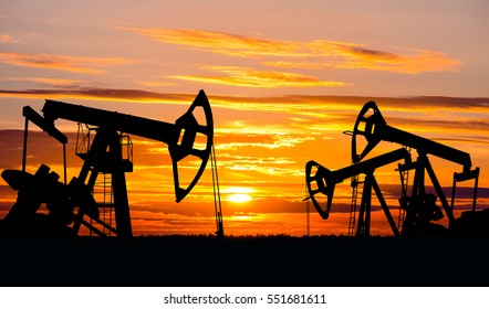 Industrial landscape. Oil Field. Oil pumps against the setting sun.