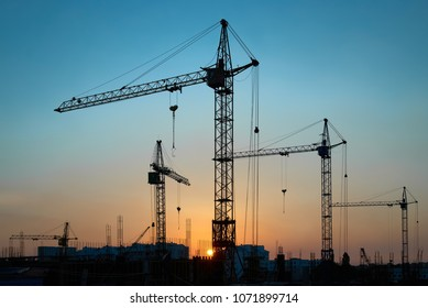 Industrial landscape with silhouettes of constraction cranes on dramatic sunset background