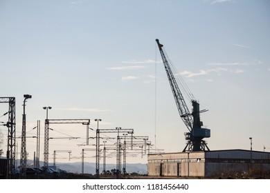 Industrial landscape at sunst, with an electrified railway line and its tracks, next to a heavy loading crane, standing next to a warehouse