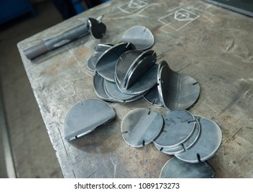 Industrial laser cut steel metal pieces in a cold hard industrial factory setting. Metal iron cut pieces being prepared for manufacture.
