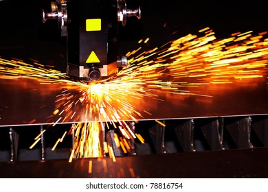 Industrial laser cuts metal with sparks flying around