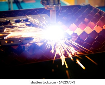 Industrial laser cutter with sparks.