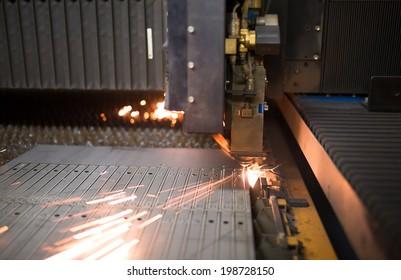 Industrial laser during cutting metal works in factory workshop