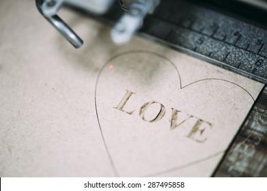Industrial laser engraving word love on a paperboard