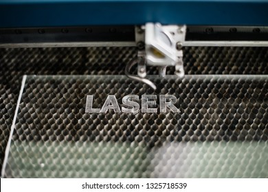"Industrial laser engraving word ""laser"" on the metal tray background, close up view"