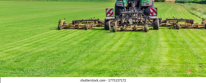 Industrial lawn mower cutting the grass in a large farm field