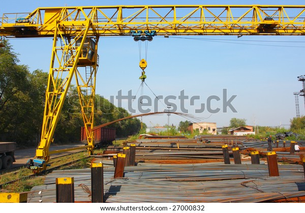 Industrial lifting crane loading bunch of steel rods in warehouse against a blue sky