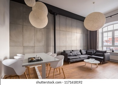Industrial living room with dining table, white chairs, corner sofa and diy ball lampshades