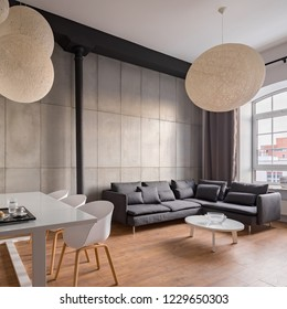 Industrial living room with dining table, white chairs and corner sofa