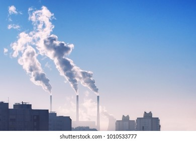 Industrial long chimneys with dark smoke going outside in the city