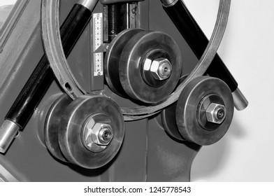 Industrial machine for bending steel pipes and metal rods. Pipe bending machine. Black and white image.