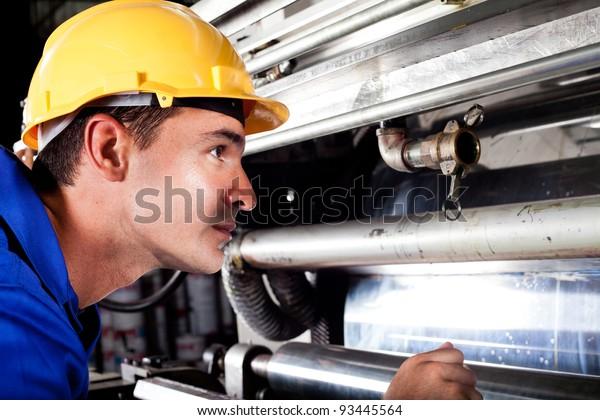 Maschinenbediener der Industrie-Maschine überprüft Maschine während sie läuft