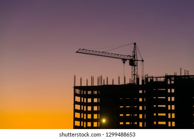 Industrial machinery and the construction crane. Cranes and skyscraper under construction, city skyline at sunset, sunrise Building under Construction site.