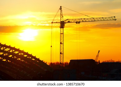 Industrial machinery, construction crane. Cranes and frame sports arena under construction, city skyline at sunset, sunrise Building under Construction site.