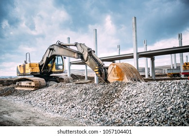 Industrial machinery on highway construction site, heavy duty excavator moving gravel and rocks for foundation building