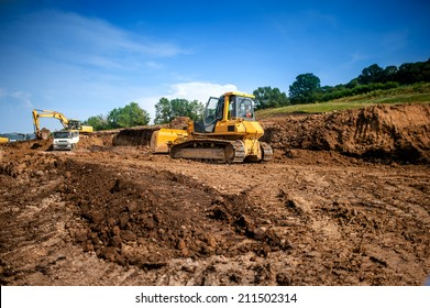 industrial machinery at working construction building site. Excavator, dumper truck and bulldozer working on ground