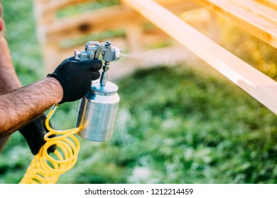 Industrial male worker painting brown timber using spray gun and air compressor