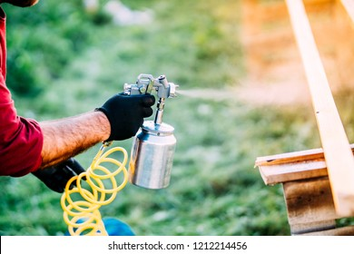 Industrial man painting brown timber using spray gun and air compressor