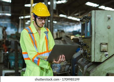 industrial man wearing uniform safety and helmet working with laptop in factory background.