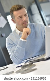 Industrial manager in office working on laptop