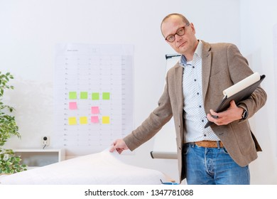 A Industrial manager who is checking and planning at the office,  with a planning board and a flipover in the background