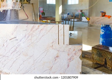 Industrial marble cutting factory of Afyonkarahisar in Turkey. The beige color marble cooling with water while being cut. A worker removing cut marble plates in the factory on the background.June 2016